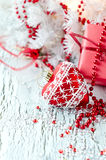 Christmas red present box with a heart decoration copy space. Greeting card for xmas on white wooden background Royalty Free Stock Photo