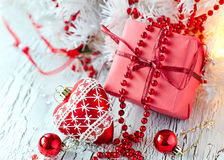 Christmas red present box with a heart shape decoration. Greeting card for xmas on white wooden background Royalty Free Stock Photography