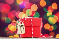 Christmas red present or box for secret santa on colorful bokeh background. Greeting card. Christmas red present or box for secret santa on colorful bokeh royalty free stock photography