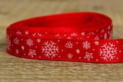 Christmas red ribbon with snowflakes and Christmas trees on a wo Stock Photography