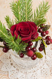 Christmas red rose and berries decorations. Christmas red rose and berries with twigs of pine tree decoration on a table royalty free stock photos