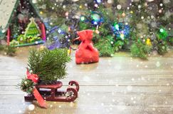 Christmas red sack with gifts on sleigh on a wooden background with spruce branches. Stock Photos