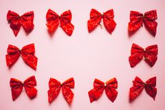 Christmas red satin bows frame, set of ribbons on pink background royalty free stock images
