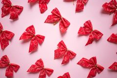 Christmas red satin bows pattern, set of ribbons on pink background stock photography