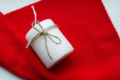 Christmas red scarf and a white candle, tied with twine, copy space. Xmas time Royalty Free Stock Photography