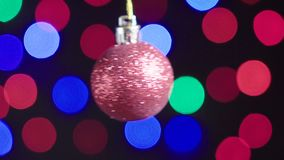 Christmas red ball toy is spinning close-up. Decor with new year tree lights twinkling on background. Christmas red shiny ball toy is spinning close-up. Decor stock video footage