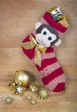 Christmas red sock with monkey and any gold balls isolated on wood surface. Royalty Free Stock Image