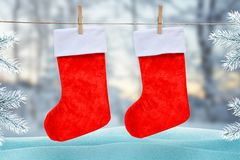 Christmas red socks hooked with a clip on a rope. Winter, snow scene with Christmas tree in background stock images