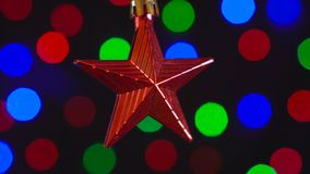 Christmas red star toy is spinning close-up. Decor with new year tree lights twinkling on background. 4k stock video