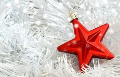 Christmas red star on white needless. Christmas red star decoration on white needless with snow flakes Royalty Free Stock Photography