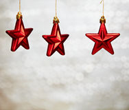 Christmas red stars. Hanging on sparkling background with bokeh effect stock photos