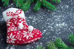 Christmas red stocking on snowbound black background with fir br Stock Image