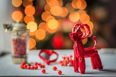 Christmas red straw goat decoration. Christmas decoration with red straw goat over the table on a lighting background Stock Images