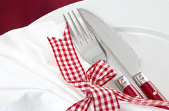 Christmas: red table setting - knife and fork checked. Close up of elegant red table setting - knife and fork for christmas Stock Photo