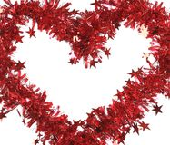 Christmas red tinsel with stars as heart. Royalty Free Stock Image