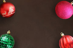 Christmas red, wavy, pink and green ribbed ball on dark wooden table Stock Images