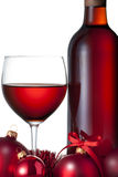 Christmas Red Wine. A close up of a bottle and glass of red wine with christmas ornaments ribbon and tinsel on a white background Stock Images