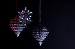 Christmas Reflections. Christmas ornaments and stars reflect silver and red against a black background Stock Photography