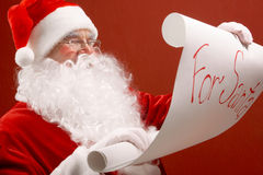 Christmas regards. Portrait of cute Santa Claus reading big letter on red background Stock Photography