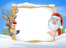 Christmas Reindeer and Santa Sign. With cute cartoon Reindeer and Santa pointing at a snow covered sign on a winter landscape Royalty Free Stock Photos