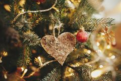 Christmas retro heart ornament on beautiful christmas tree with. Golden lights. handmade vintage toy and glowing illumination in festive room. decor for winter royalty free stock photo