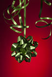 Christmas ribbon. Green Christmas ribbon and bow with red background Royalty Free Stock Images