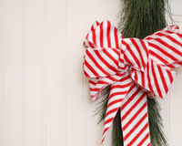 Christmas Ribbon On Beadboard. A red and white striped Christmas ribbon and real garland on a beadboard background with room for copyspace Stock Images