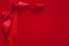 Christmas ribbon with bow on red fabric Stock Photos