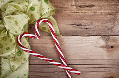 Christmas ribbon and candy canes on wooden background Stock Photography
