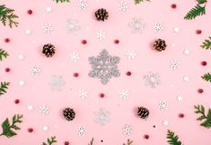 Christmas ring composition. Pattern with snowflakes, cones, red berries and tree branches on pastel pink background and big silver royalty free stock photos