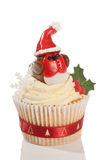 Christmas Robin Cupcake. Christmas cupcake decorated with homemade fondant icing robin wearing a santa hat on white background stock photo