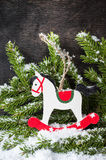 Christmas rocking horse and spruce branches with snow. Stock Images