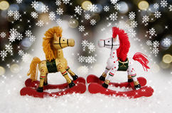 Christmas Rocking Horses. Two ornamental Christmas rocking horses facing each other with snowflake and bokeh background Stock Photo