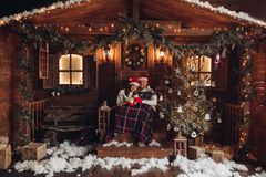 Christmas romance in Santa Claus hats beautiful house New Year`s atmosphere royalty free stock photography