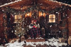 Christmas romance in Santa Claus hats beautiful house New Year`s atmosphere. Christmas romance in Santa Claus hats. A happy couple with coffee are sitting near royalty free stock photo