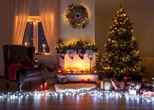Beautiful decorated living room with a christmas tree and a fire place. Christmas room beautiful decorated, warm with fire place , christmas tree and many lights stock photo
