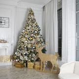 the Christmas room decoration. Spruce with gifts. Wooden figures of deer with light. Fireplace decorated with a wreath and candles stock photo