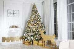 the Christmas room decoration. Spruce with gifts. Wooden figures of deer with light. Fireplace decorated with a wreath and candles royalty free stock photography