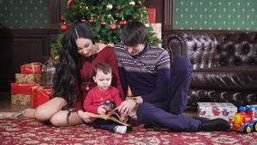 Christmas room. The family has gathered around a New Year tree. The kid holds the book in hand. Careful parents read to stock video footage