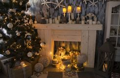 Christmas room with fireplace, presents under decorated fir tree Royalty Free Stock Image
