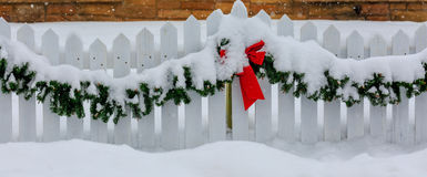 Christmas Roping in Snow. White picket fence decorated for Christmas with red bow and green garland in the snow Royalty Free Stock Photography