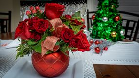 Christmas Red Rose Floral Arrangement Background. Christmas Rose Floral Arrangement on dining table with Christmas Tree ornament in background royalty free stock images