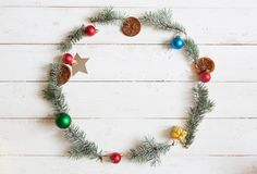 Christmas round frame. Fir branches, christmas poinsettia on wooden white background. Flat lay, top view.  royalty free stock photography