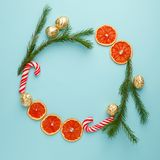 Christmas round frame made of natural pine branches, traditional xmas sweetness candy cane and candied fruit citrus on blue. Background. Flat lay, top view stock photography