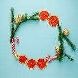 Christmas round frame made of natural pine branches, traditional xmas sweetness candy cane and candied fruit citrus on blue backgr. Ound. Flat lay, top view royalty free stock image