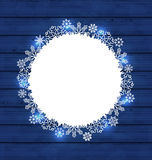Christmas round frame made in snowflakes on blue wooden backgrou Royalty Free Stock Photo