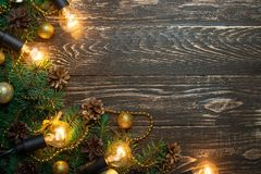 Christmas rustic background - old wooden board with backlight and branches of a Christmas tree and shyshkami and a free text space. Christmas rustic background stock photos