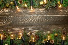 Christmas rustic background - old wooden board with backlight and branches of a Christmas tree and shyshkami and a free text space. Christmas rustic background royalty free stock images