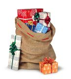 Christmas sack full of presents isolated. Santas Christmas present burlap sack full of beautiful present boxes isolated on white royalty free stock photos