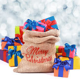 Christmas sack overflowing with colorful gifts Royalty Free Stock Images